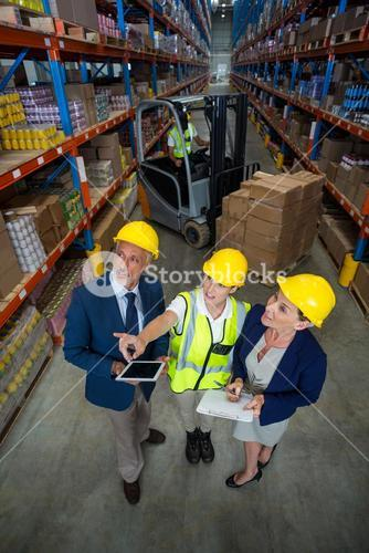 High angle view of worker showing shelves to managers