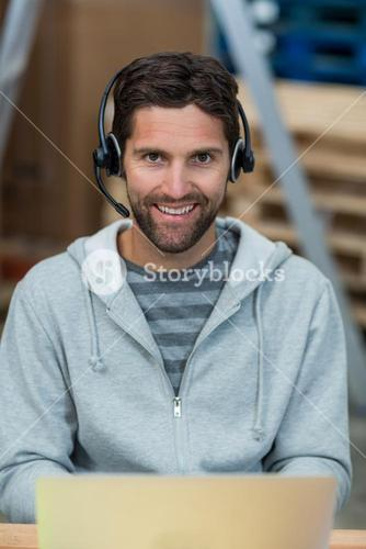Portrait of a smiling worker wearing a headset