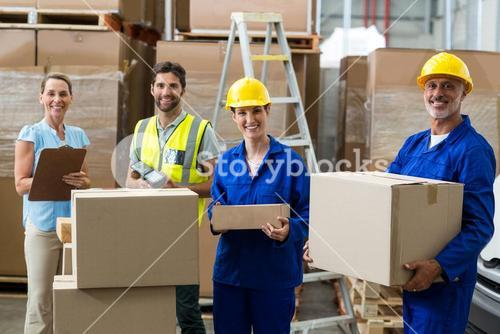 Smiling workers carrying boxes
