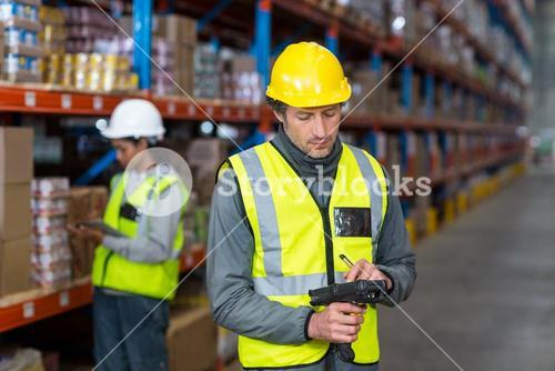 Worker checking stock with digital equipment