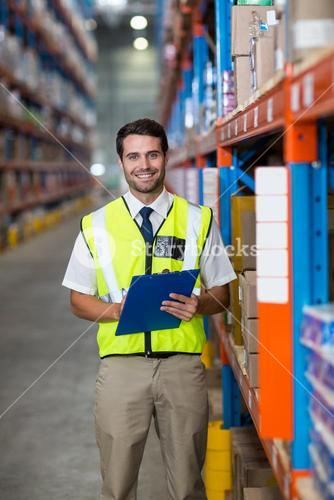 Worker with clipboard looking at camera
