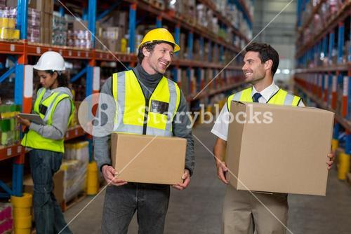 Workers holding box looking each other