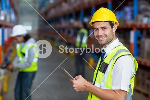 Worker in warehouse looking at camera