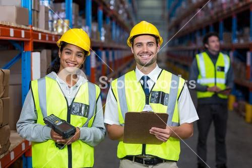 Smiling worker wearing yellow safety vest looking at camera