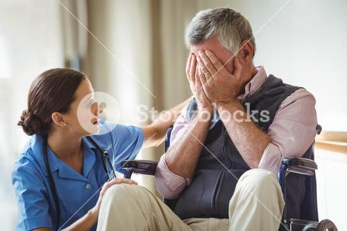Nurse taking care of sad senior man