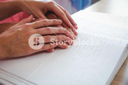 Nurse helping senior woman with braille