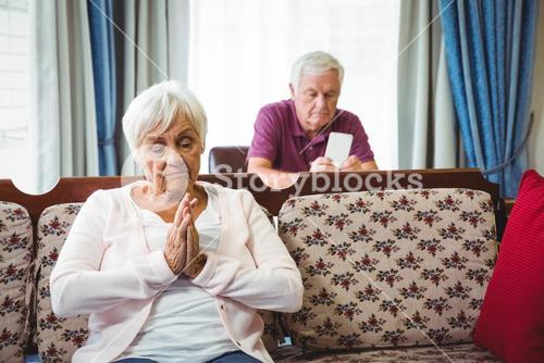 Serious seniors sitting on couch and chair