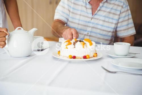 Patient is cutting the cake