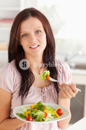 Woman with salad looking into camera