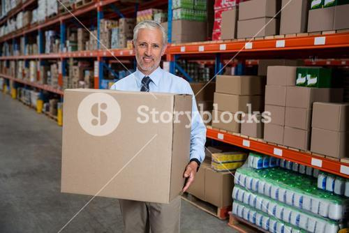 Smilng worker holding boxes