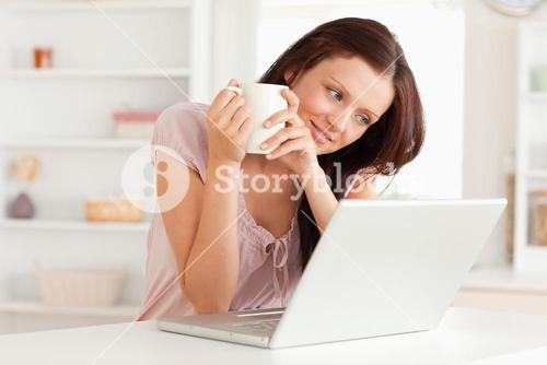 Woman with cup of coffee and laptop