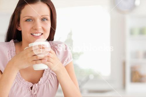 Woman with cup of coffe looking