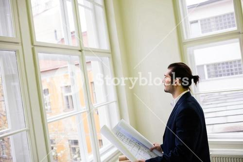Interior designer holding blueprint while looking through window