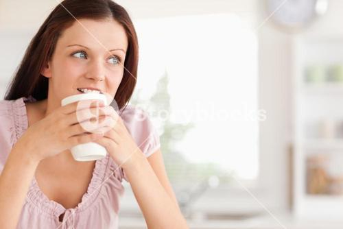 Woman with cup of coffe looking away