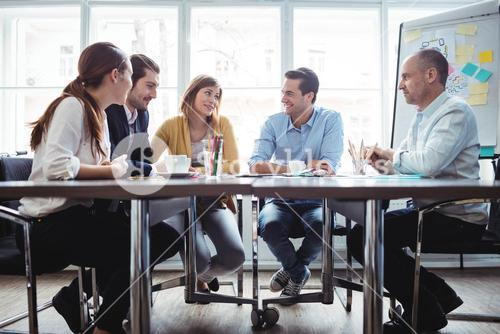 Coworkers discussing in meeting room