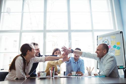 Colleagues high-five in meeting room