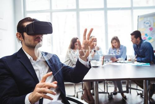 Businessman using virtual reality simulator against colleagues