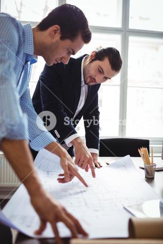 Interior designer discussing blueprint with male coworker