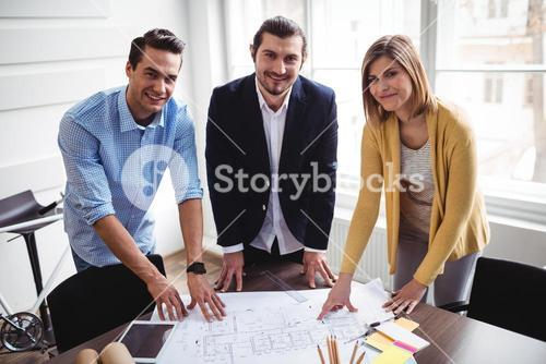 Smiling business people with blueprint