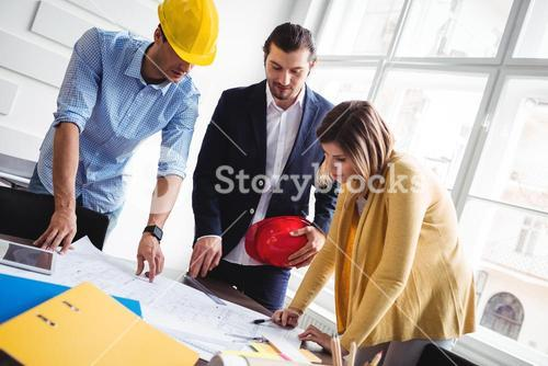 Tilt image of business people looking at blueprint