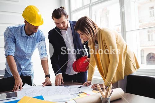 Business people with blueprint on table