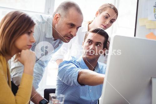 Business people discussing using laptop