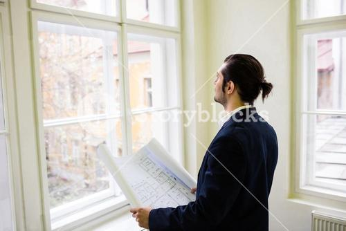 Interior designer with blueprint looking though window