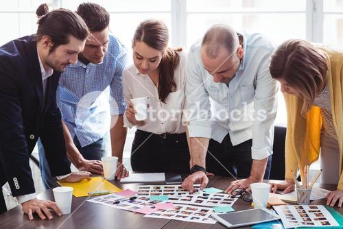 Photo editors looking at photos on table