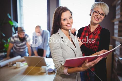 Happy female coworkers standing with file in creative office