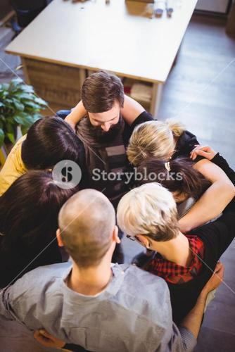 Creative business people forming huddle in office
