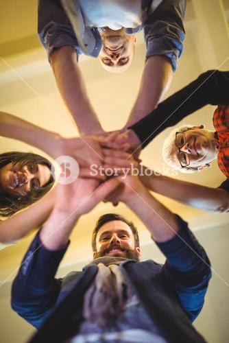Happy business people stacking hands in creative office
