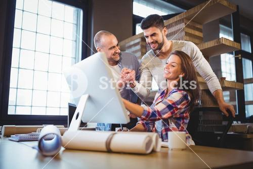 Business people looking at computer in creative office