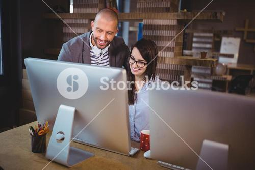 Business people smiling while looking at computer