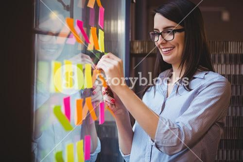 Creative businesswoman sticking adhesive notes to glass in office