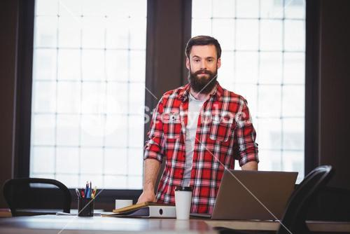 Hipster standing by desk in creative office