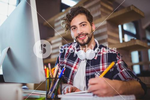 Portrait of creative businessman writing in spiral notebook