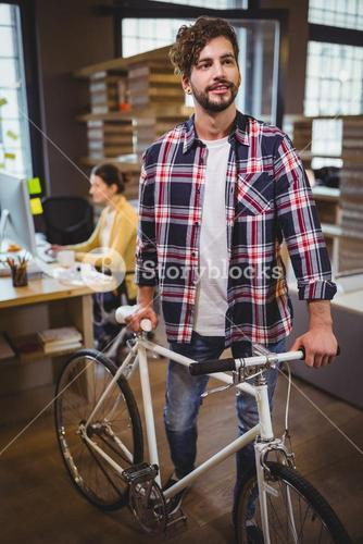 Creative businessman standing by bicycle in office
