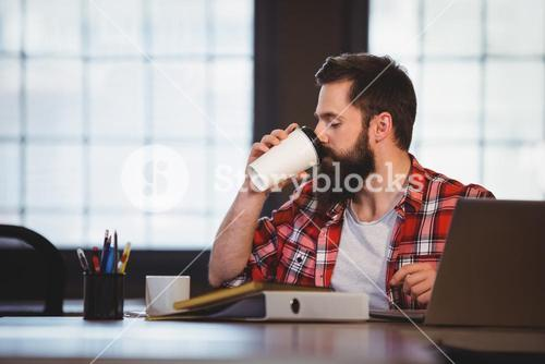 Hipster drinking coffee at desk