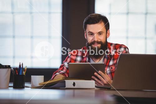 Hipster using digital tablet in creative office