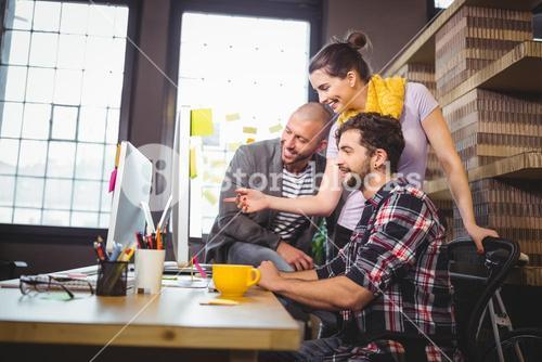 Coworkers working at computer desk