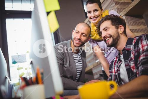 Happy coworkers at computer desk in office