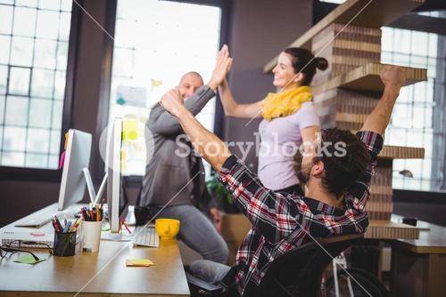 Business people cheering at computer desk