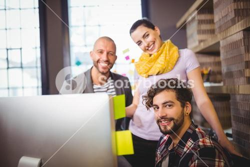 Happy creative business people by computer