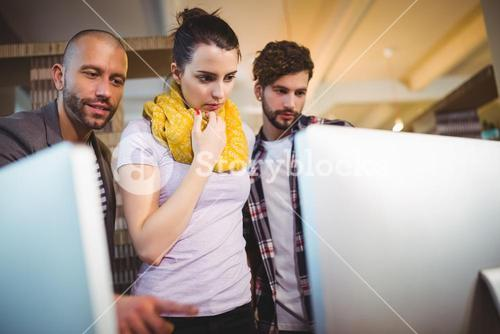 Creative business people looking in computer monitor