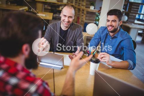 Business people smiling discussing at desk