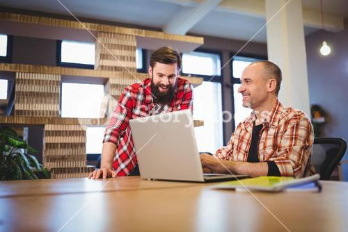 Creative male coworkers discussing over laptop