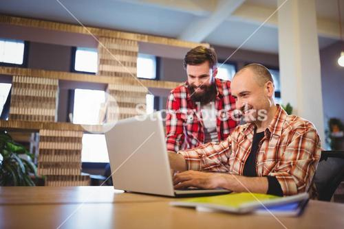 Male colleagues smiling while discussing over laptop