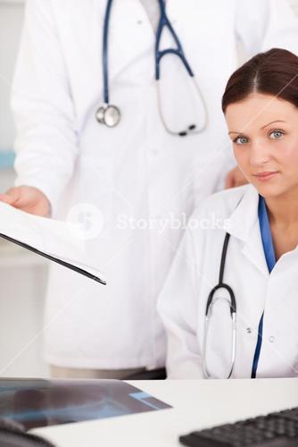Doctor showing female doctor a file in office