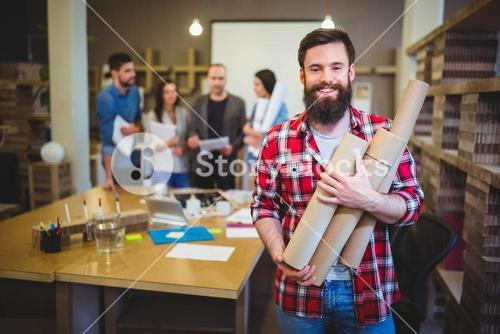 Architect holding blueprint tubes while standing by table