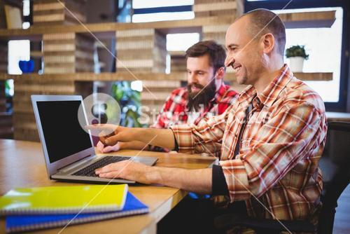 Creative male colleagues smiling while discussing over laptop